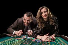 有演奏轮盘赌的妇女的人在赌博娱乐场 对的瘾 免版税库存照片
