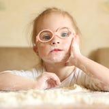 有演奏面粉的唐氏综合症的女孩 库存照片