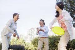 有演奏飞碟的祖父母的微笑的孙女在公园 免版税库存照片