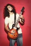 有演奏guit的美丽的长的卷发的热情的吉他弹奏者 库存图片