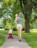有漫步在公园的孩子的妇女 免版税库存照片