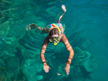 有潜航在清楚的水中的面具的妇女 图库摄影