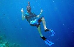 有潜航潜水的风镜和的飞翅的一个人在水面下 库存图片
