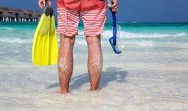 有潜航的齿轮的人在他的站立在一个Maldivian海滩的手上 库存照片