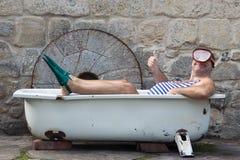 有潜航的齿轮的人在浴缸 免版税库存照片