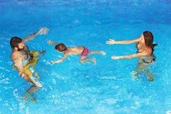 有潜水在水面下在室外水池的父母的婴孩 免版税库存照片