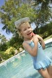 有潜水面具的在游泳池边的女孩和废气管 库存照片
