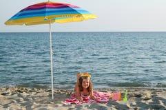 有潜水面具的小女孩在海滩的遮光罩下 免版税图库摄影