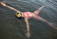有潜水面具的小女孩,当漂浮在海水时 库存图片