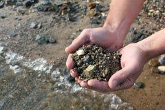 有潮湿的河沙子的男性棕榈反对水 免版税库存照片