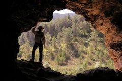 有澳大利亚帽子和背包的探险家在洞的入口观看森林的 免版税库存图片