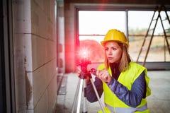 有激光的少妇工作者在建筑工地 免版税库存照片