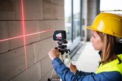 有激光的少妇工作者在建筑工地 图库摄影