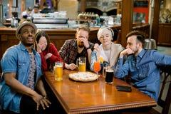 有激动的不同的朋友在一起吃比萨的电视饮用的啤酒的乐趣观看的体育比赛网上录影,五 库存照片