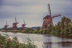 有灌木和风车的运河在小孩堤防的多云天 免版税库存图片