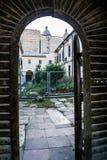 有灌木的修道院围场通过古老的木门 库存图片
