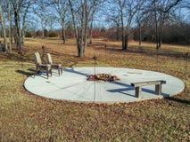 有火坑的一个圆的水泥露台在中间和一个长木凳和被堆积的椅子和金属tiki火炬在wi离开了 免版税图库摄影