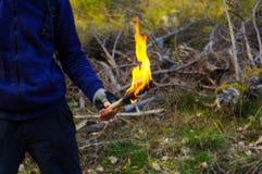 有火炬的一部分的一个人和手在狂放的自然背景中发火焰 免版税库存图片