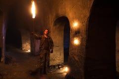 有火炬的人探索古老被放弃的地下寺庙 库存照片