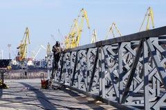 有火炬的工业焊工和防护盔甲在焊接大发怒建筑的海口 库存照片