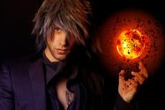 有火球的英俊的巫术师 免版税库存照片