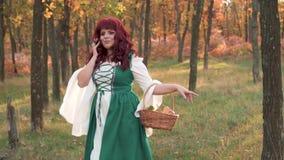 有火红的头发的逗人喜爱的可爱的大女孩在秋天森林里,享受早晨太阳和光的光芒 股票录像