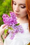 有火红的头发的美丽的性感的妇女在有淡紫色和白色礼服的庭院里有美好的构成的 免版税库存照片