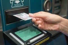有火车票的特写镜头手从自已服务机器 免版税库存照片