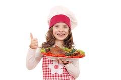 有火鸡鼓槌和赞许的小女孩厨师 免版税库存图片