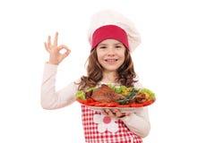 有火鸡鼓槌的小女孩厨师和好手签字 免版税库存照片