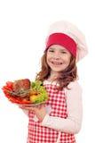 有火鸡鼓槌的小女孩厨师 免版税图库摄影