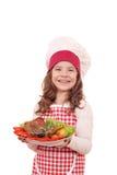 有火鸡鼓槌的小女孩在盘的厨师和沙拉 免版税库存照片