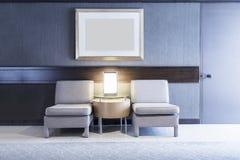 有灯和空白的照片框架的沙发在墙壁在有光的屋子里 免版税库存照片