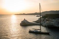有灯塔的Madonetta航行游艇在黄昏的Bonifacio市附近 免版税库存照片