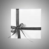 有灰色丝带的被隔绝的假日礼物白色箱子在梯度背景 库存图片