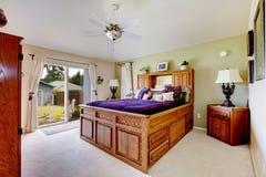 有灰色地毯、吊扇和紫色卧具的主卧室 免版税库存图片