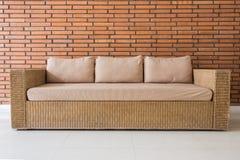 有灰色坐垫和红砖墙壁的藤条沙发 免版税图库摄影