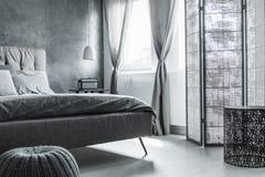 有灰色墙壁的舒适的卧室 免版税库存图片