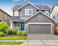 有灰色外部的现代房子和蓝色白色修剪 免版税库存照片