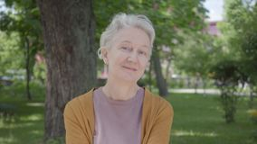 有灰色头发和蓝眼睛的微笑在绿色惊人的公园的美丽的老妇人画象  可爱成熟 股票视频