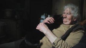 有灰色头发的一个老妇人在一个被放弃的村庄拿着她的在她的胳膊的恶意嘘声,与她的戏剧,微笑,生活 股票视频