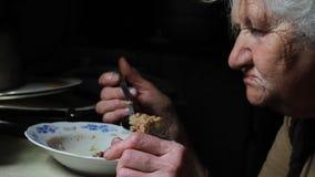 有灰色头发的一个老妇人在她的老被毁坏的房子里吃着从一块板材的一个袋子,生活在一个被放弃的村庄 股票录像