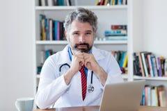 有灰色头发的严肃的男性医生 免版税库存照片