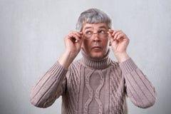 有灰色看头发佩带的镜片的一名神奇老人在旁边 接触他的玻璃的聪明的成人考虑somethin 库存照片