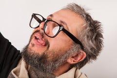 有灰色胡子的疯狂的看起来的老人与书呆子大玻璃 免版税图库摄影