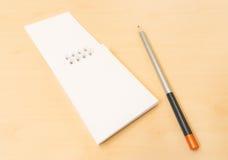 有灰色铅笔被安置的木表的白色笔记本 库存照片