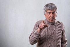 有灰色头发和大开眼睛的一个积极的成人人指向您的有手指的 情感老人佩带的毛线衣standi 库存照片