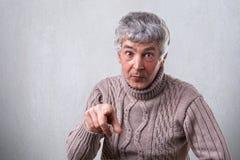 有灰色头发和皱痕的使表示惊奇的可爱的老人画象指向您有他的食指的 免版税库存图片