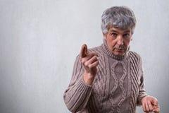有灰色头发的一个吃惊的英俊的年长人在毛线衣穿戴了站立在白色墙壁附近指向与手指的要说 库存照片