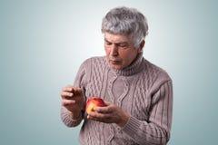 有灰色头发的一个成熟人在毛线衣穿戴了拿着一个被损坏的苹果看它殷勤地审查它的 老人藏品 免版税库存图片